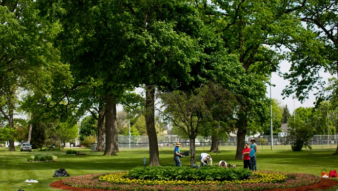 Volunteers from the Blue Water Garden Club work at Pine Grove Park in Port Huron. The volunteers planted nearly 200 flats of flowers in the park.