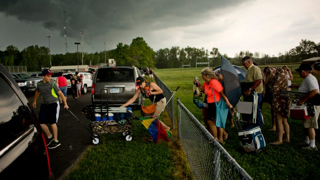 Spectators run to their cars as a storm approaches during a division 2 softball and baseball finals Saturday, May 30, 2015 at Algonac High School.