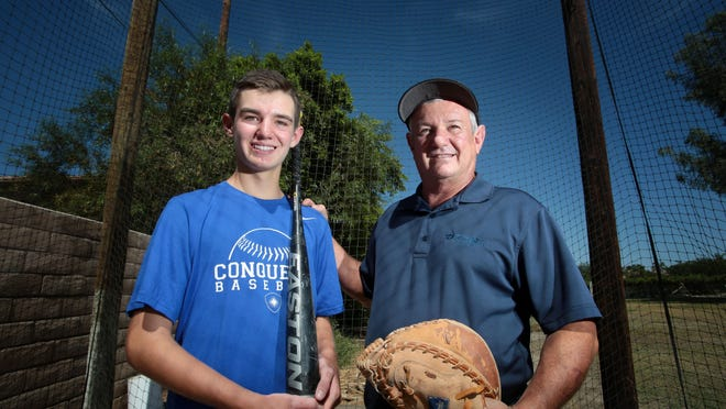 Jeff Percy with his son Ryan Percy in the family batting cage at their  Bermuda Dunes home on Tuesday. Ryan is a pitcher at Desert Christian Academy and Jeff is a coach.