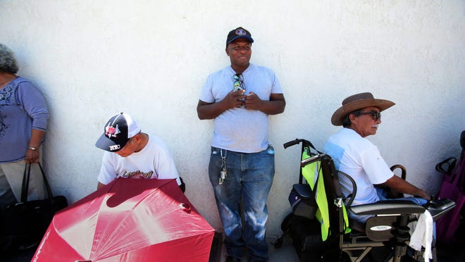 Gregg Grace, center, of Desert Hot Springs, in line to pick up food on Tuesday at the St. Margaret's Outreach Center on San Pablo Avenue in Palm Desert. The center is closing and St. Margaret's is opening a new outreach program on the church campus in August.