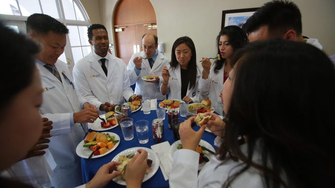 Eight residents from the UC Riverside School of Medicine's Family Medicine Residency program are welcomed into Desert Regional Medical Center during a lunch and ceremony on Wednesday.