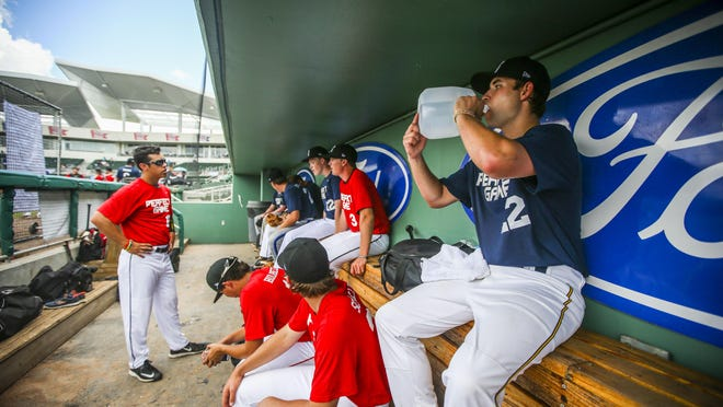 Garrett Stallings of Chesapeake, Va., drinks from a gallon jug of water to keep hydrated at the Perfect Game Tournament while other players take shelter from the sun in the dugout.