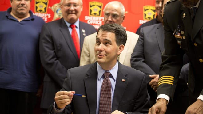 Wisconsin Gov. Scott Walker signs a gun bill on Wednesday, June 24, at the Milwaukee County Sheriff's office that eliminates a 48-hour waiting period for handgun purchases.