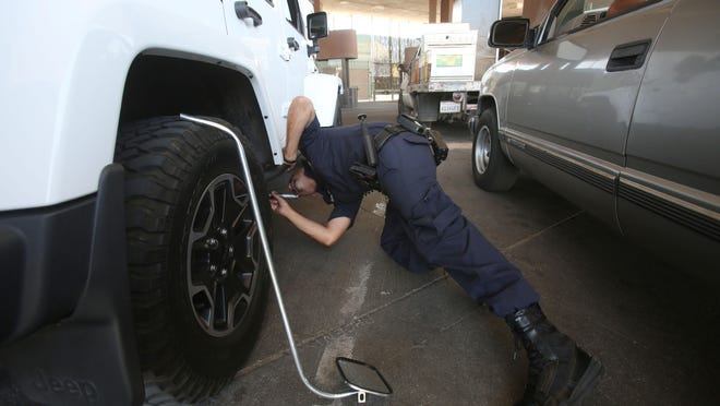 A Customs and Border Protection Officer manually inspects a vehicle at the Calexico point of entry into the United States. Calexico processes 4 million vehicles and 4.1 million pedestrians per year.