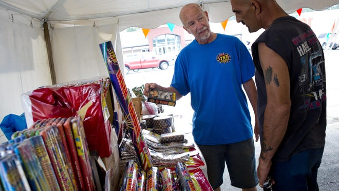 Rob Neumann of Port Huron shows a customer his selection of fireworks Tuesday at the corner of South Range Road and Gratiot Boulevard in Marysville.