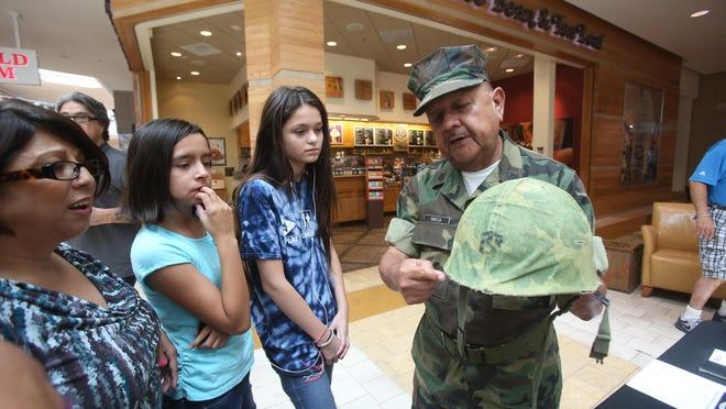 Vietnam Veteran Aaron Garcia demonstrates the type of helmet he used in Vietnam to, from left, María Garcia, Melissa Ramirez and Yesenia Ramirez during a memorial held at Westfield Mall in Palm Desert on July 3.