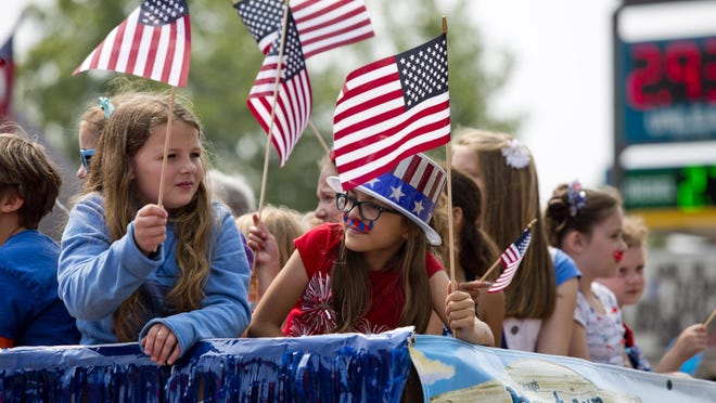 Kids wave flags on a float for Lexington Vacation Bible School during the 2015 Fourth of July parade in Lexington.