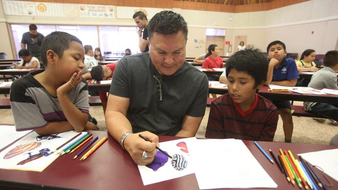 Educator Simon Silva demonstrates a drawing technique to, from left, Angel Candelario and Juan Mulato at Toro Canyon Middle School in Thermal as part of a student and parent workshop offered to migrant farmworker families.