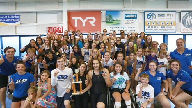 The EDGE Swim Club poses with its first place trophy at the Vermont Swim Association state championships meet on Saturday at the Upper Valley Aquatic Center in White River Junction.