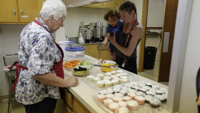 Betty Hawley serves Jennifer Jones and a child as they participate in the lunchtime meal at Christ Lutheran Church. Christ Lutheran Church is serving a free lunch to families from 11 a.m. to 1 p.m. They are filling the gap where the Oshkosh Area School District left off by serving families until school resumes in September.