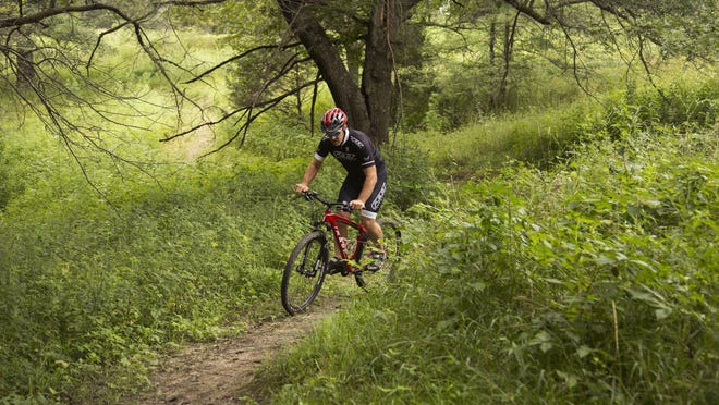 Rich Pross of Audubon, Iowa, demonstrates how to bike on one of the mountain biking trails at Whiterock Conservancy in Coon Rapids, Iowa, on Tuesday, Aug. 4, 2015.