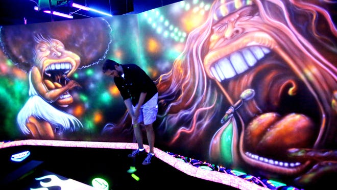 Columnist Shad Powers tries out the miniature golf course under the black lights in La Quinta at the Rock 'N' Roll MiniGolf. He putts as Aerosmith's Steven Tyler and Tina Turner look on.