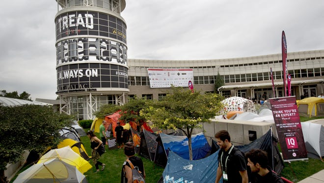 This Aug. 5, 2015, file photo, shows attendees of the Outdoor Retailer Show viewing the camping tent display area of the event in front of the Salt Palace Convention Center, in Salt Lake City.