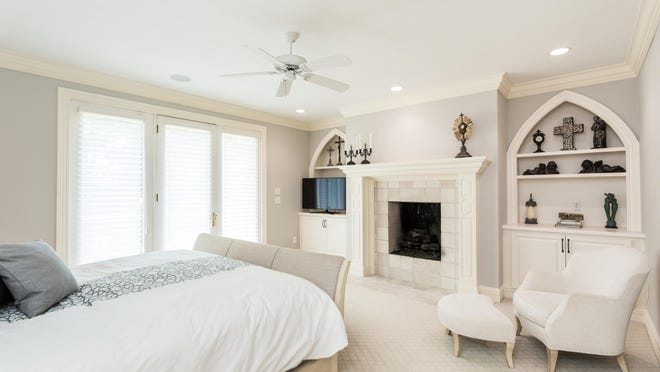 The master bedroom is a calm retreat with a fireplace and balcony.