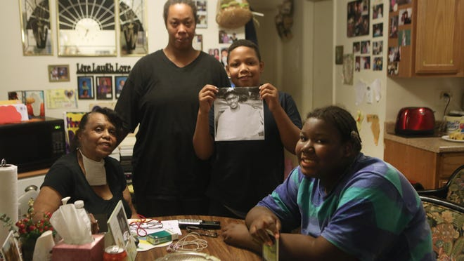 Family members of Barry Washington, (from left) mother Amanda Washington, sister Jaci Washington, nephew Alex and niece Amanda, talk in the kitchen of Amanda's Madisonville apartment. Barry Washington, 56, died at the Elks Club in Madisonville one Friday night last month after being caught in the crossfire of one of the city's biggest shootouts of the past eight months. He had stopped in the lodge to use the restroom on his walk to the store.