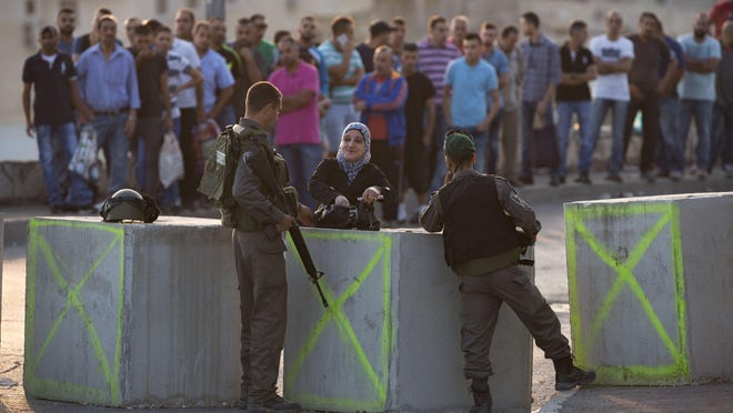 Israeli border police check a Palestinian woman's identification Sunday at a checkpoint in the Arab neighborhood of Issawiyeh in Jerusalem.