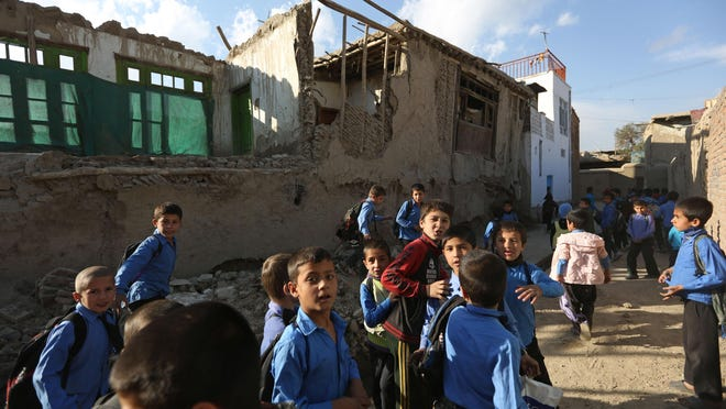 Afghan school boys tour the neighborhood to look at damaged houses following a powerful earthquake today that could be felt across South Asia, in Kabul, Afghanistan, Monday, Oct. 26, 2015. In Afghanistan's Takhar province, west of Badakhshan, at least 12 students at a girls' school were killed in a stampede as they tried to get out of the shaking buildings, a local official says. Sonatullah Taimor, the spokesman for the Takhar provincial governor, says another 30 girls have been taken to the hospital in the provincial capital of Taluqan. (AP Photo/Rahmat Gul)