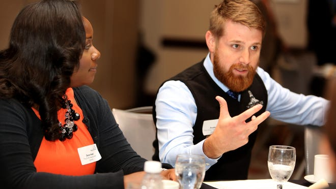 Dayna Harper, left, listens to Brad Jackson, both of The Christ College of Nursing and Health Sciences in a table discussion during Diverse by Design: 2015 Leadership Symposium at the Hyatt Regency Tuesday October 27, 2015.