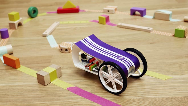 The BitBot toy is made of brightly colored components that connect together easily with magnets, then attach to mounting boards like Legos.
