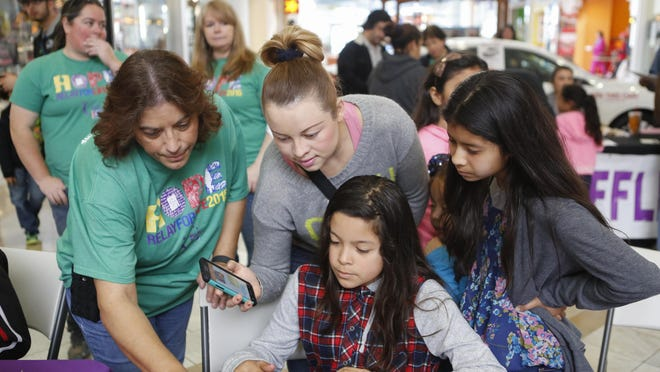Mirna Hills of Team First Capital Bank helps a family during a signup process during an American Cancer Society Relay For Life of Salinas fundraising event at Nothridge Mall on Saturday, January 30, 2016 in Salinas, Calif. Vernon McKnight/for The Californian