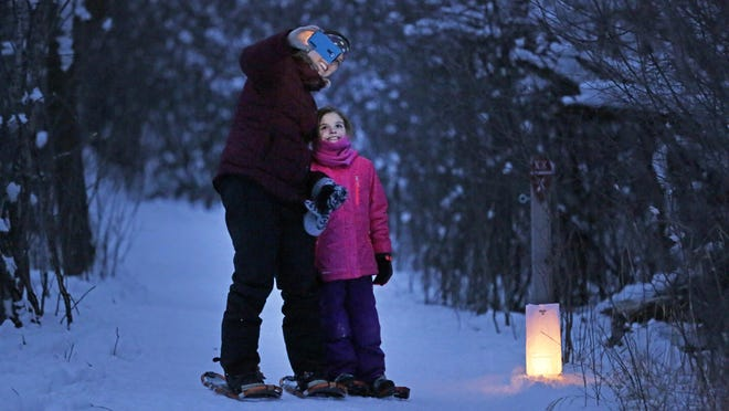 Amanda Feller of Menasha and her daughter, Jaelyn, take a selfie on Feb. 5 to commemorate their first time on snowshoes during the Moonlight Ski, with some help by candlelight, at Gordon Bubolz Nature Preserve in Appleton.