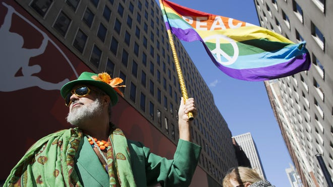 Steven Menendez waves a gay pride flag as he waits for the St. Patrick's Day parade to start on Fifth Avenue on Thursday.