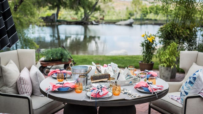 """At Robin Mercer and Ed Morgan's west Reno compound, a table for six is set on a circular stone terrace lying next to one of the ponds. Marcio Decker of Aspen Leaf Interiors used linen wingback chairs and upmarket nautical accents to create an """"indoors outside"""" look for Mercer's seafood lunch."""