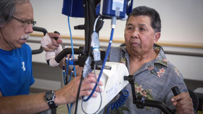 Phoukham Tran using a functional electrical stimulation therapy bike Thursday with Peter Langston, a medical program instructor at the YMCA Healthy Living Center in Clive.
