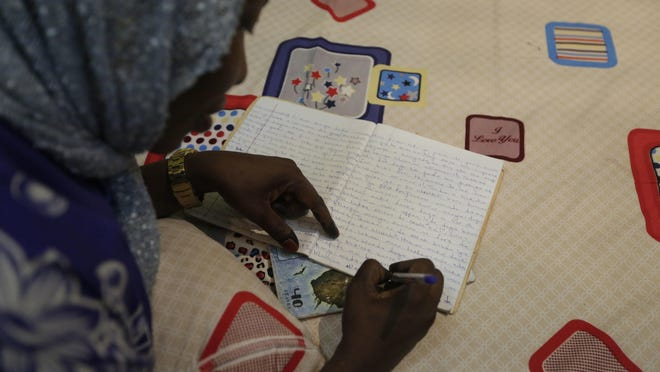 In this photo taken Tuesday April, 5. 2016 author Hadiza Nuhu Gudaji, composes a novel while resting on her bed with an exercise book and a ballpoint pen in Kano, Nigeria. In the local market stalls are signs of a feminist revolution with piles of poorly printed books by women, as part of a flourishing literary movement centered in the ancient city of Kano, that advocate against conservative Muslim traditions such as child marriage and quick divorces. (AP Photo/Sunday Alamba)