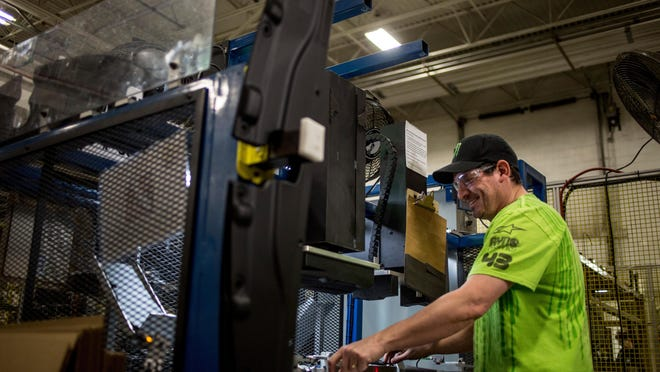 Michael Henry uses equipment to assemble an automotive component earlier this month at US Farathane Corporation in Port Huron.