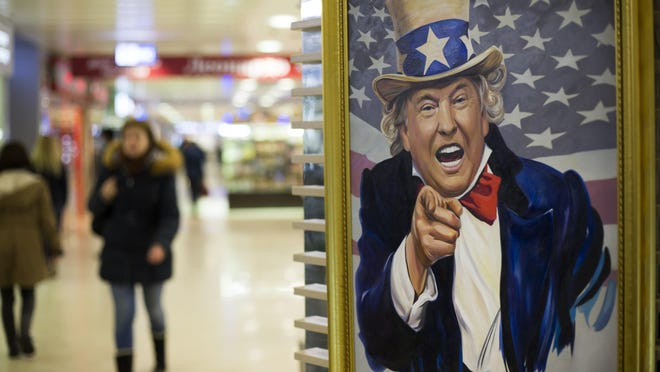 People walk past a caricature picture of U.S. President Donald Trump on sale in a shopping mall in Moscow, Russia, Wednesday, March 22, 2017. (AP Photo/Alexander Zemlianichenko)