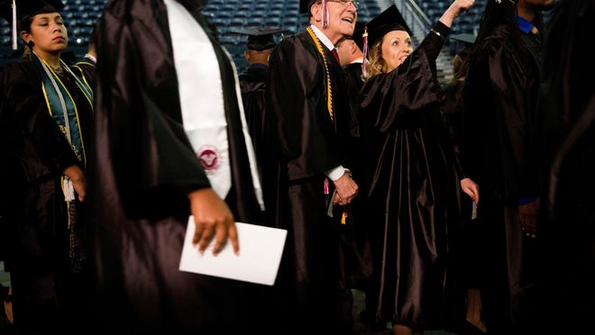 Nic Neumann, 77, along with friend Iliana Mramorenska, point out visitors who have come to see them while waiting to make their entrance for the Hodges University graduation ceremony at Germain Arena on Sunday.