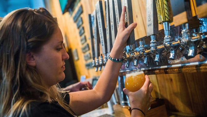 Chelsea Fischer fills a drink for a customer at Palm City Brewing Co. in San Carlos Park.