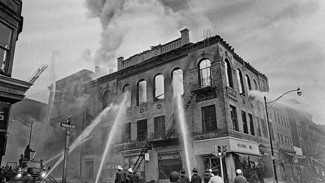 Firefighters direct streams of water onto a burning building July 15, 1967, in Newark, N.J., where four days of deadly violence and looting came to be known as the Newark riots.