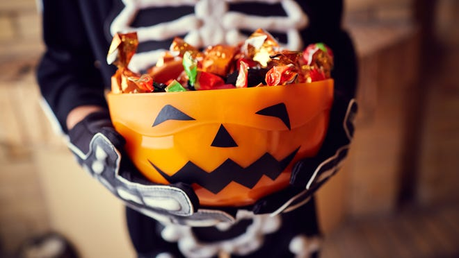 Boy in skeleton costume holding bowl full of candies. (Getty Images)
