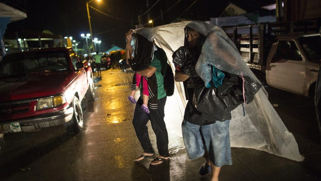 Central American migrants take cover from a heavy rain in Mapastepec, Mexico, Oct. 24, 2018.