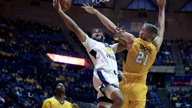 West Virginia forward Esa Ahmad (23) drives to the basket while being defended by Valparaiso center Derrik Smits (21) during the second half of an NCAA college basketball game Saturday, Nov. 24, 2018, in Morgantown, W.Va. (AP Photo/Raymond Thompson)