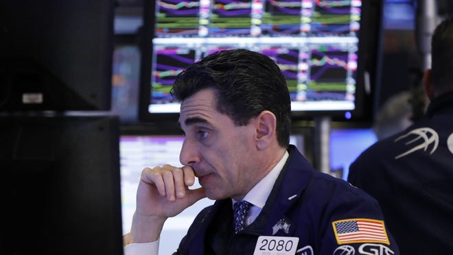 Specialist Peter Mazza works at his post on the floor of the New York Stock Exchange.
