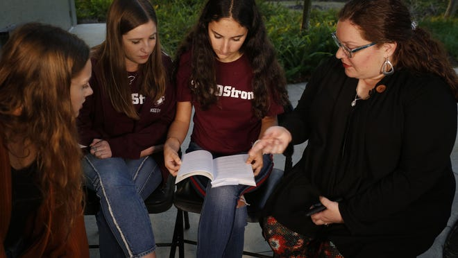 """In this Wednesday, Jan. 16, 2019, photo, Brianna Jesionowski, from far left to right, Brianna Fisher and Leni Steinhardt sit during an interview with The Associated Press as journalism teacher Sarah Lerner, right, makes a point regarding the new book called """"Parkland Speaks: Survivors from Marjory Stoneman Douglas Share Their Stories,"""" in Parkland, Fla. Students and teachers from the Florida school where 17 died in February's high school massacre wrote the raw, poignant book about living through the tragedy. (AP Photo/Brynn Anderson)"""