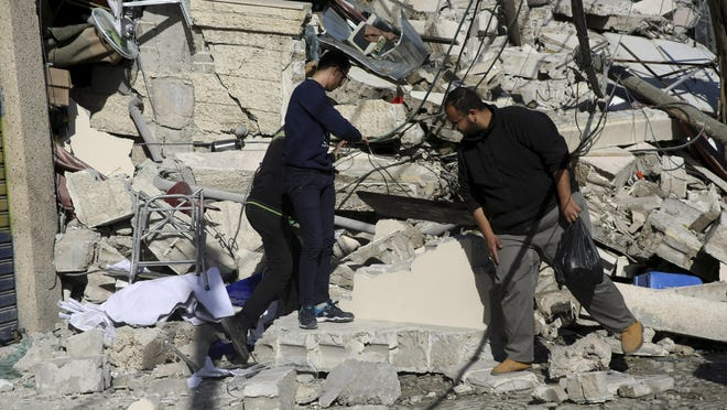 Palestinians inspect the damage of the destroyed multi-story building of Hamas-affiliated insurance company, in Gaza City, Tuesday, March 26, 2019.