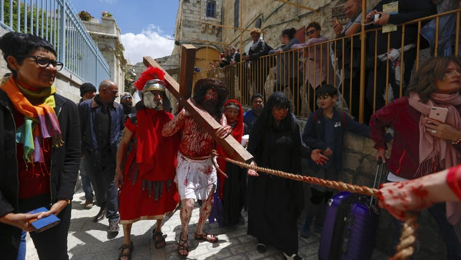 An actor dressed as Jesus Christ carries a cross as he reenacts the crucifixion walk along the Via Dolorosa towards the Church of the Holy Sepulchre, traditionally believed by many to be the site of the crucifixion of Jesus Christ, during the Good Friday procession in Jerusalem, Friday, April 19, 2019. (AP Photo/Ariel Schalit)