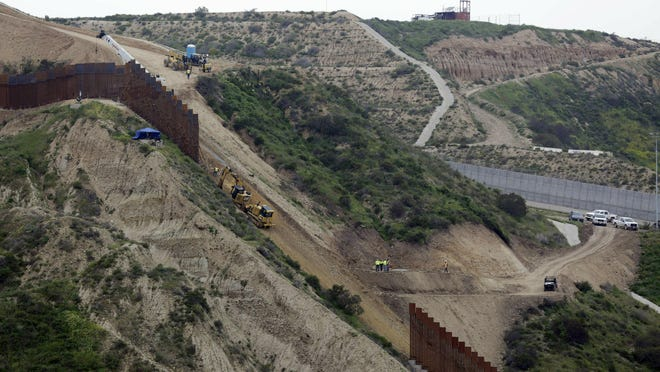 FILE - In this March 11, 2019 photo, construction crews replace a section of the primary wall separating San Diego, above right, and Tijuana, Mexico, below left, seen from Tijuana, Mexico. Defense Secretary Mark Esper has approved the use of $3.6 billion in funding from military construction projects to build 175 miles of President Donald Trump's wall along the Mexican border. (AP Photo/Gregory Bull, File)
