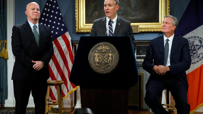 New York City Police Commissioner James O'Neill, left, listens as his successor, Chief of Detectives Dermot Shea, center, speaks at New York City Hall on Monday, alongside Mayor Bill de Blasio.