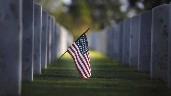 An American flag hangs near a headstone at the South Florida National Cemetery for Veterans Day on Sunday, Nov. 10, 2019, in Lake Worth, Fla. (AP Photo/Brynn Anderson)