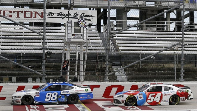 Chase Briscoe (98) crosses the finish line ahead of Kyle Busch to win the NASCAR Xfinity series auto race Thursday in Darlington, S.C. The race started after a rain delay of 4½ hours. AP Photo/Brynn Anderson