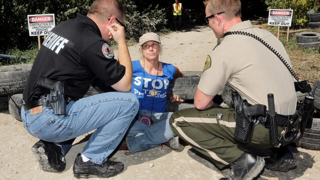 Activist Jessica Reznicek, is shown protesting in Oct. 5, 2016 as she talks with Stacy Weber, with the Lee County Sheriffs Department, left, and deputy Dakota Foley while blocking the entrance to a pipeline construction site along the Mississippi River road between Montrose and Keokuk.