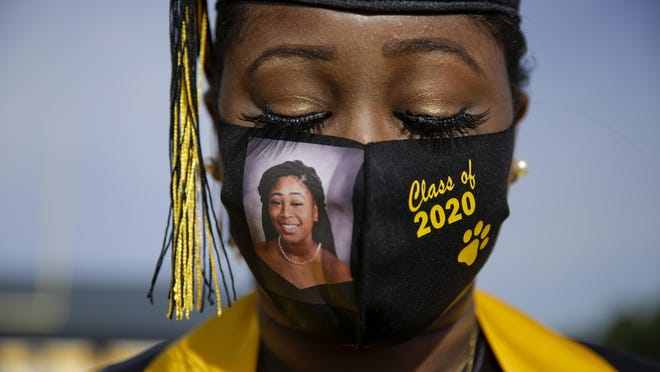 A member of the Class of 2020 wears a photo of herself on her protective mask amid the coronavirus pandemic as she graduates with limited classmates and family attending the ceremony last month in Georgia.