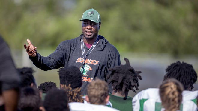 Atlantic High School football team head coach TJ Jackson talks to his players at practice on August 8, 2019 in Delray Beach, Florida.