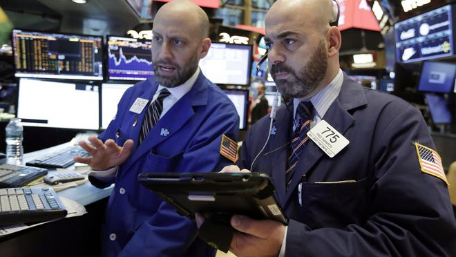 NEW YORK -- Specialist Meric Greenbaum, left, and trader Fred DeMarco work on the floor of the New York Stock Exchange Wednesday as the market pushes into record territory again.