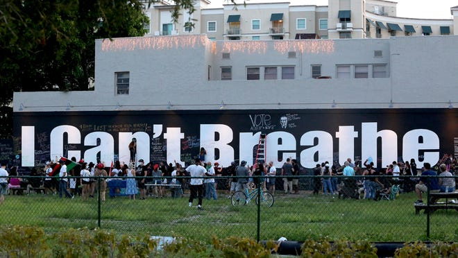 """Hundreds of people participated in  """"Chalk the Block"""" at the """"I Can't Breathe"""" mural near the 500 block of Clematis Street Friday evening. People were encouraged to write positive messages on the wall to condemn police violence and the killing of George Floyd by Minneapolis police."""